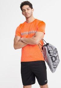 Superdry - SUPERDRY TRAINING LIGHTWEIGHT T-SHIRT - Print T-shirt - bright havana orange - 2