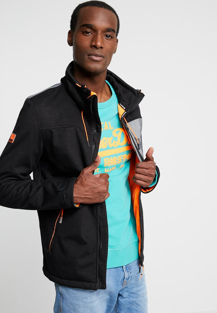 Superdry - ATOMIC WINDTREKKER - Leichte Jacke - black/bright orange