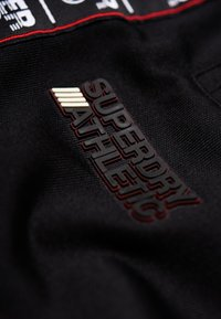 Superdry - Pantalones deportivos - track black/track red - 4