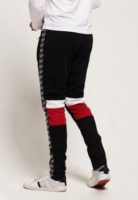 Superdry - Pantalones deportivos - track black/track red - 1