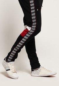 Superdry - Pantalones deportivos - track black/track red - 2