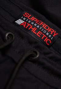 Superdry - Pantalones deportivos - track black/track red - 3