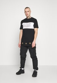 Supply & Demand - POWER CURVE HEM WITH CHEST  - T-shirt z nadrukiem - black/gold - 1