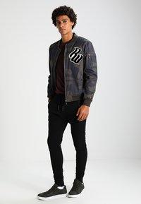Tigha - TREVOR ZIP - Pantalon de survêtement - black - 1
