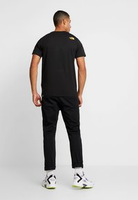 The North Face - SHOULDER LOGO TEE - T-shirt imprimé - black/yellow - 2