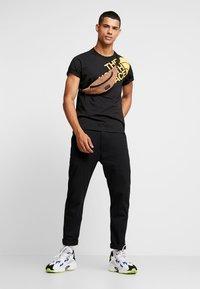The North Face - SHOULDER LOGO TEE - T-shirt imprimé - black/yellow - 1