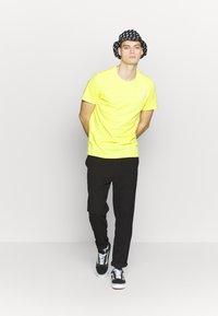 The North Face - T-shirt z nadrukiem - lemon/white - 1