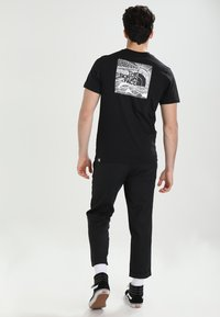 The North Face - CELEBRATION TEE - T-shirt z nadrukiem - black - 2