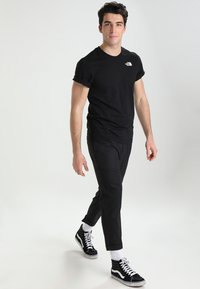 The North Face - CELEBRATION TEE - T-shirt z nadrukiem - black - 1