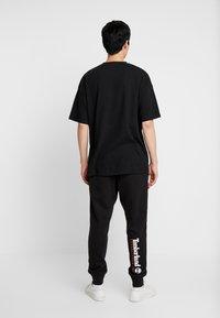 Timberland - CORE ESTABLISHED 1973 - Pantalon de survêtement - black - 2