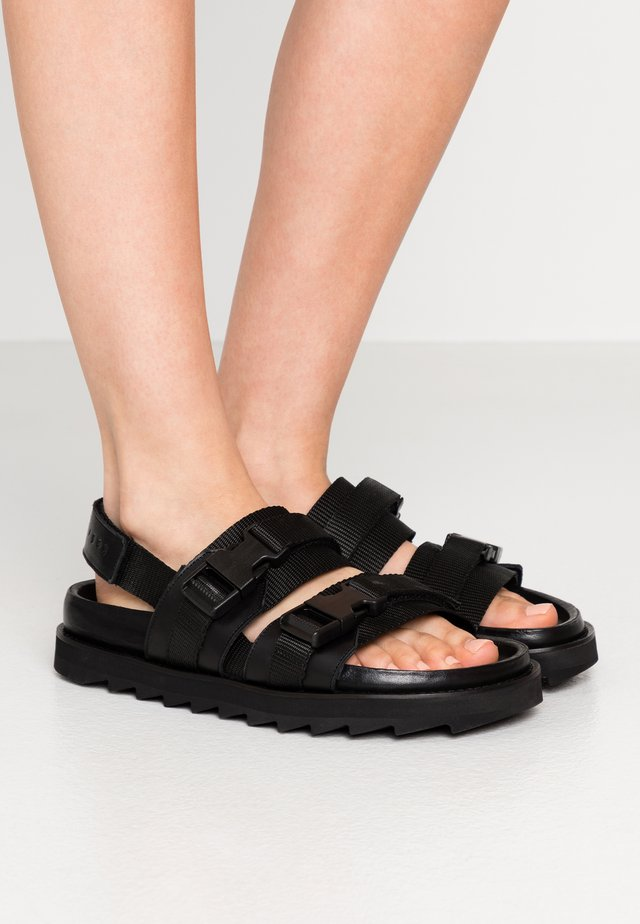 SEQUI - Sandaalit nilkkaremmillä - black