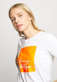 Tommy Hilfiger - ALISSA REGULAR - Triko s potiskem - white / orange