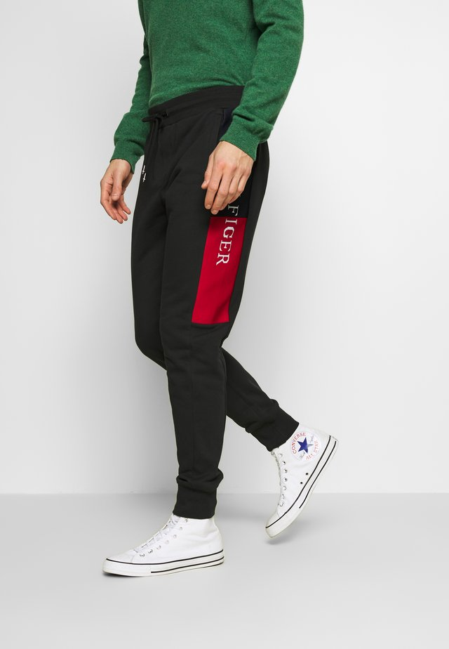 INTARSIA - Tracksuit bottoms - black
