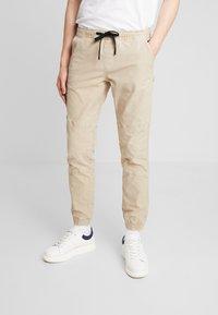 TOM TAILOR DENIM - JOGGERFIT - Pantalones - ecru brown - 0