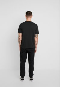 Tommy Jeans - BADGE PANT - Tracksuit bottoms - black - 2