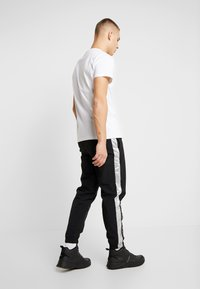 Tommy Jeans - TJM METALLIC BLOCK PANT - Trainingsbroek - black - 2