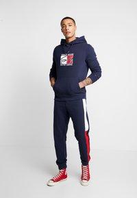 Tommy Jeans - TJM JACQUARD FLAG  - Trainingsbroek - black iris - 1
