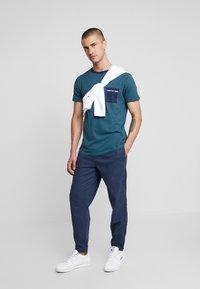 Tommy Jeans - POCKET STRIPE TEE - T-shirt con stampa - atlantic deep/black iris - 1