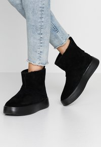 UGG - CLASSIC BOOM BOOT - Platform ankle boots - black - 0
