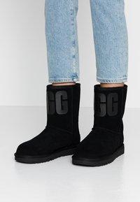 UGG - CLASSIC SHORT LOGO - Kotníkové boty - black - 0