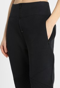 Under Armour - UNSTOPPABLE MOVE LIGHT REACTOR PANT - Tracksuit bottoms - black - 5