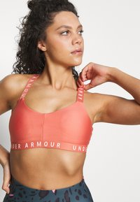 Under Armour - WORDMARK STRAPPY SPORTLETTE - Urheiluliivit - blush orange/peach frost