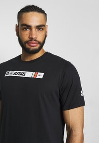 Under Armour - TEE - T-shirt med print - black/white/gravity green - 3