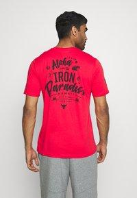 Under Armour - PROJECT ROCK IRON PARADISE  - Camiseta de deporte - versa red/black - 2