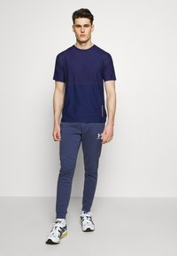 Under Armour - SPORTSTYLE - Tracksuit bottoms - blue ink/onyx white - 1