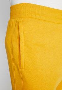 Under Armour - RIVAL WORDMARK LOGO - Verryttelyhousut - golden yellow/white - 5