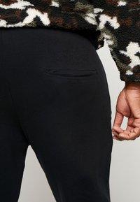 Urban Classics - FORMULA CROPPED PEACHEDINTERLOCK PANTS - Bukse - black - 3
