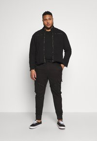 Urban Classics - TACTICAL TROUSER - Cargo trousers - black - 1
