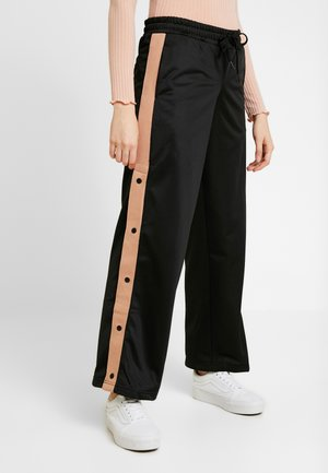 NATIVE TRACK - Tracksuit bottoms - black