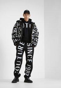 Versace Jeans Couture - JOGGERS - Pantalon de survêtement - black - 1
