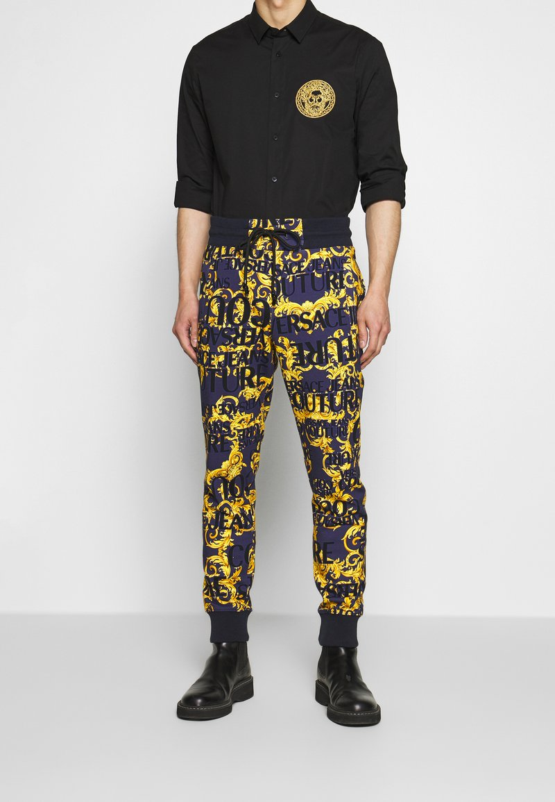 Versace Jeans Couture - ALLOVER PRINT JOGGERS - Trainingsbroek - blue