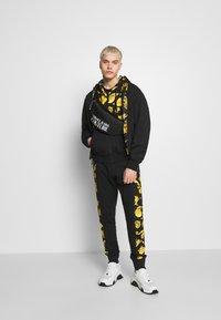 Versace Jeans Couture - JOGGERS GIOIELLI SIDE STRIPE - Pantaloni sportivi - black - 1