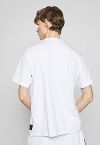 Versace Jeans Couture - FOIL LOGO WITHOUT THE 'BE BAROQUE' PATCH REGULAR FIT - T-shirt con stampa - white - 2