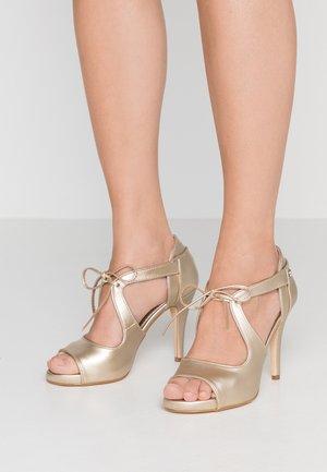 Korolliset sandaalit - metall gold