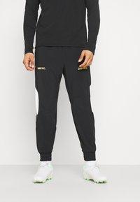 Nike Performance - FC PANT - Tracksuit bottoms - black/white/saturn gold - 0