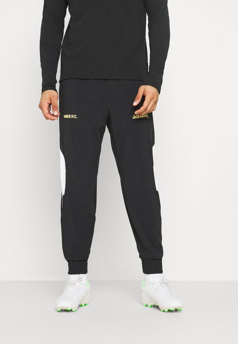 Nike Performance - FC PANT - Tracksuit bottoms - black/white/saturn gold