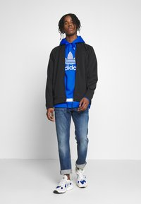 adidas Originals - WARMUP - Training jacket - black/goldmt - 1