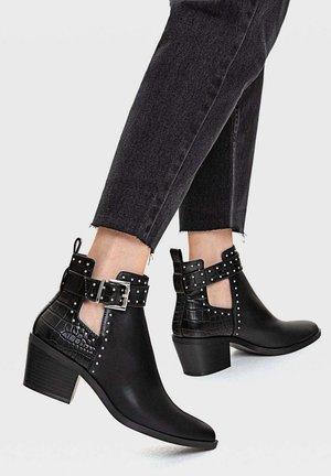 MIT CUT-OUTS UND NIETEN - Ankle boots - black