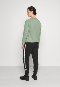 Nike Sportswear - REPEAT - Tracksuit bottoms - black - 2