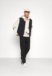 Pegador - SUEDE BUTTON PANTS UNISEX - Trousers - black - 4