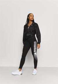 Puma - GRAPHIC LEGGINGS - Collants - black - 1