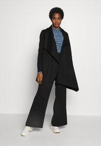 Selected Femme - SLFMAYA FLARED SLIT PANT - Stoffhose - black - 1
