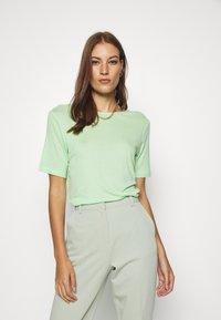 Moss Copenhagen - MONA DEEP BACK TOP - Basic T-shirt - pistachio green - 0