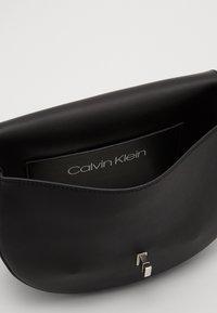 Calvin Klein - RE LOCK SADDLE BAG - Sac bandoulière - black - 4