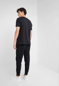 HUGO - DOAK - Tracksuit bottoms - black - 2