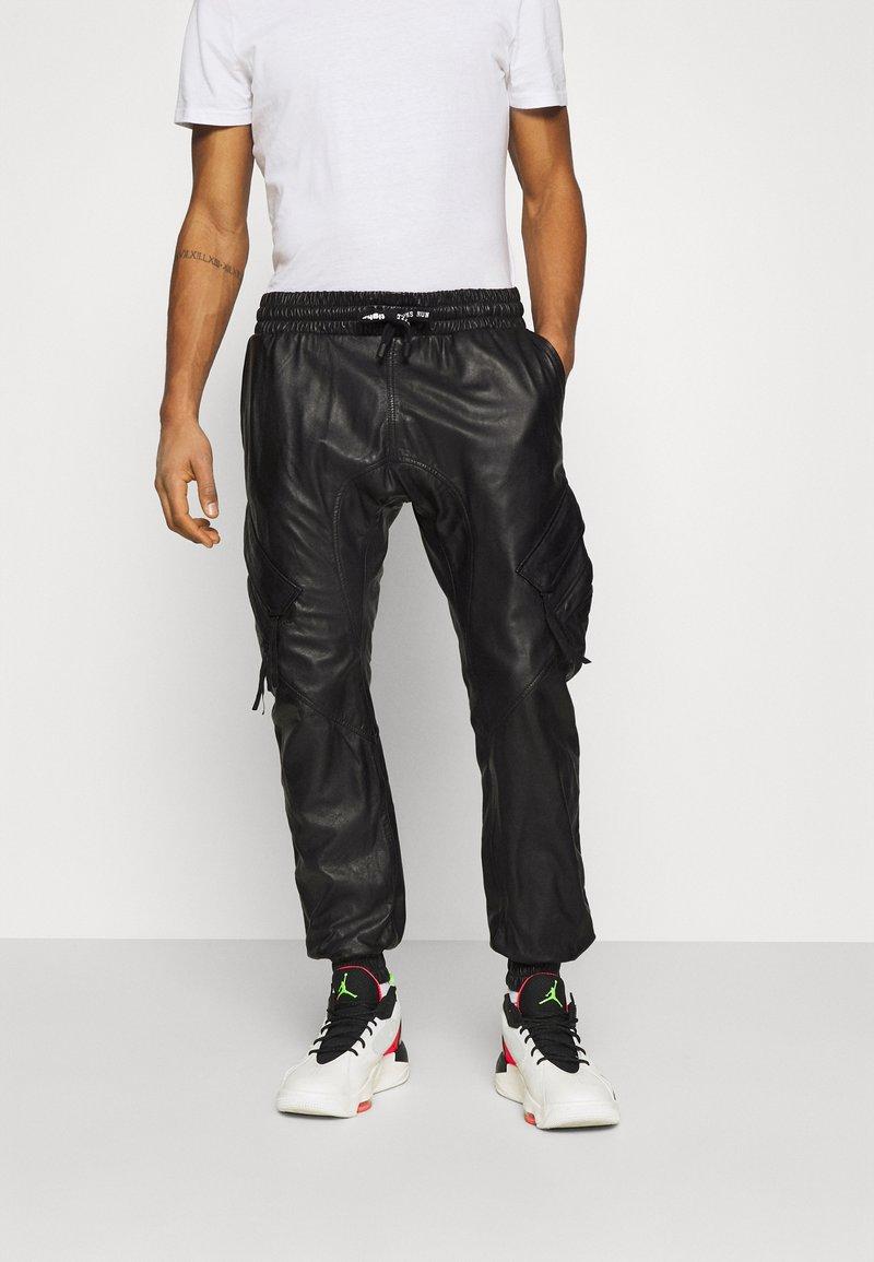 Tigha - TANO - Leather trousers - black